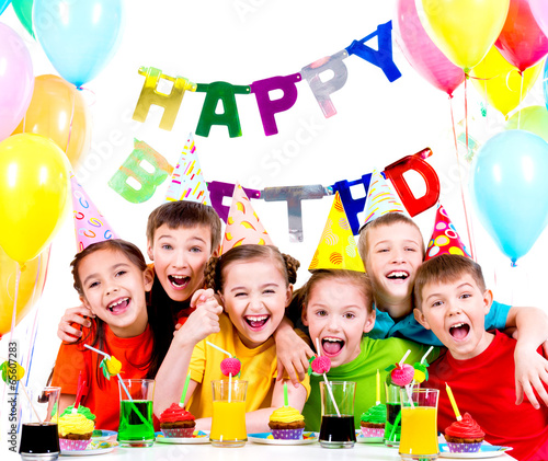 Group of laughing kids having fun at the birthday party. - 65607283