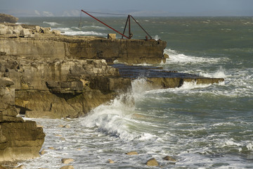 Crashing waves, rocks and a boat crane, Portland Bill