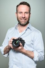 Gut aussehender Fotograf mit einem Lächeln