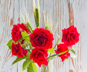 Bouquet of red roses with green ears of wheat