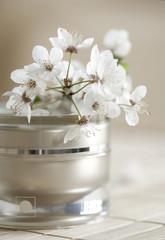 Pojemnik z kremem i białe kwiaty