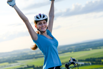healthy cheerful young woman riding mountain bike outdoor