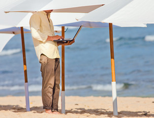 young man working remotely under the umbrella
