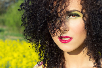 young beautiful girl in the field with bright makeup