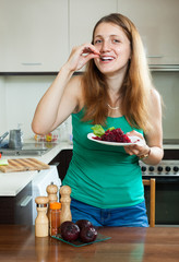 Happy ordinary woman in green eating  beets