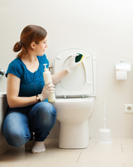 Young woman cleaning toilet bowl