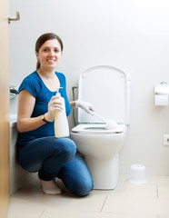 Smiling young girl  cleaning toilet bowl