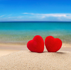 Two red hearts in the sand
