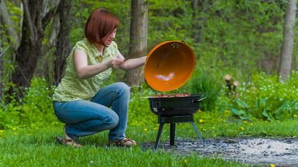 Young woman grilling liver in the park in summer