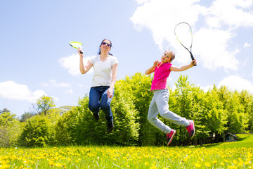 Mother and daughter playing speedminton in the park, jumping