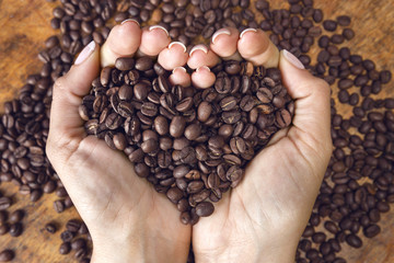 Heart shaped coffee beans,handheld.