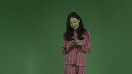 young asian adult woman in pajamas isolated on green-screen