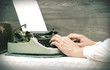 Hands typing on a typewriter