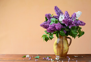 Violet and white lilacs in a vase of ceramics