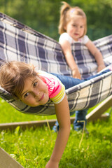 Young girl lying on hammock with other girl standing behind