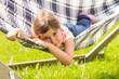 Preschool girl lying alone on hammock