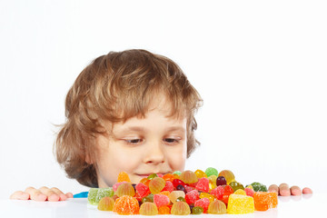 Little child with jelly candies on a white background