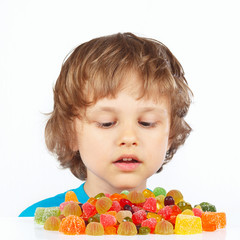 Little child with colored jelly candies on a white background