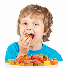 Little child eating candies on a white background