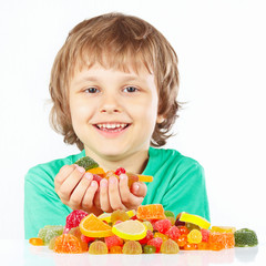 Smiling boy with sweets and candies on a white background