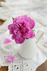 Pink peony flower in  jug on vintage lace tablecloth