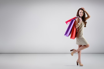 Beautiful young fashion woman posing at studio with shopping bag