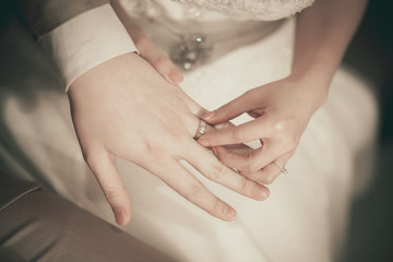 The bride wearing a wedding ring for her groom