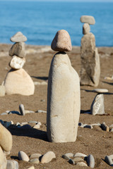 balanced stones, pebbles stacks against blue sea