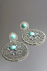 Silver earrings on grey background.