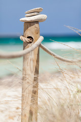 Stones balanced on wooden banister. Trucadors beach. Formentera.