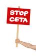 Person hält Schild mit der Aufschrift Stop CETA