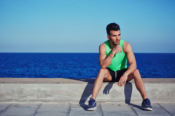 Athletic man after jogging sits on a sea background