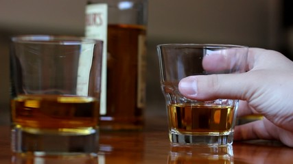 hand with glass of whiskey