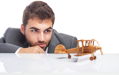 business man looking a wooden airplane on white background