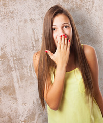 portrait of pretty young woman with her hand covering her mouth