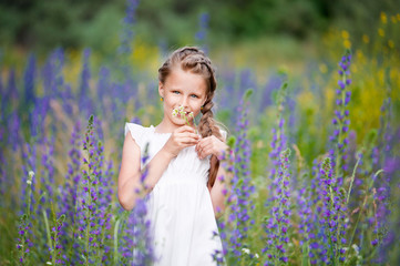 Girl in a white dress on a flower meadow