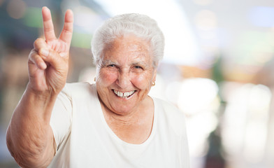 pretty old woman doing a victory gesture closeup