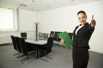 Successful young business woman,inside meeting room,smiling.