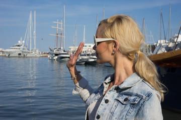 Woman standing waving overlooking a harbour