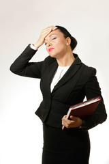 Young business woman, holding her head,looking stressed.