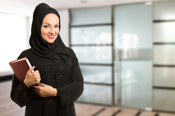 Arabic woman, traditional dressed, standing in front of office.