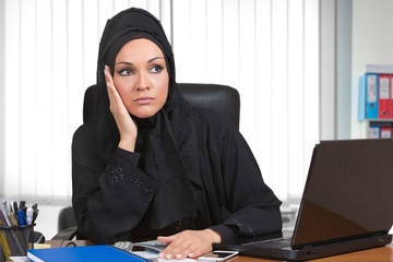 Worired arabic woman, traditional dressed, at desk office