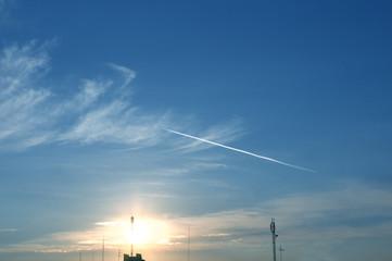 Jet plane flying highly in the sky against sunrise
