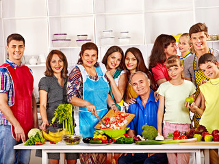 Happy family  with child and grandparent cooking at kitchen.