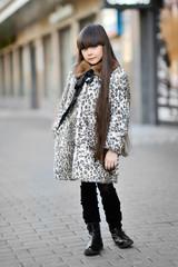 Portrait of a little girl in a fur coat