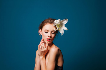 Young beautiful girl with a white lily on blue