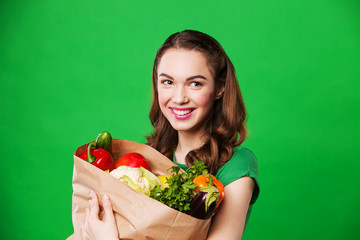 beautiful woman holding a bag full of vegetables