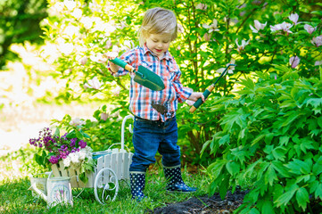 Cute kid digging in the garden with proper utensils
