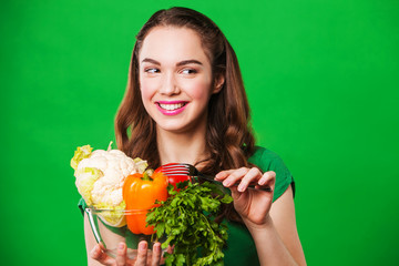 smiling woman with vegetables. on green