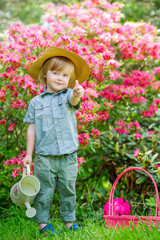 Smiling boy in the blooming garden with thumbs-up